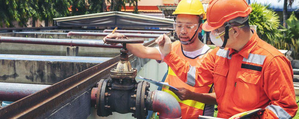 Maintenance technician inspecting wastewater treatment equipment (credit: bunyarit/Adobe Stock)
