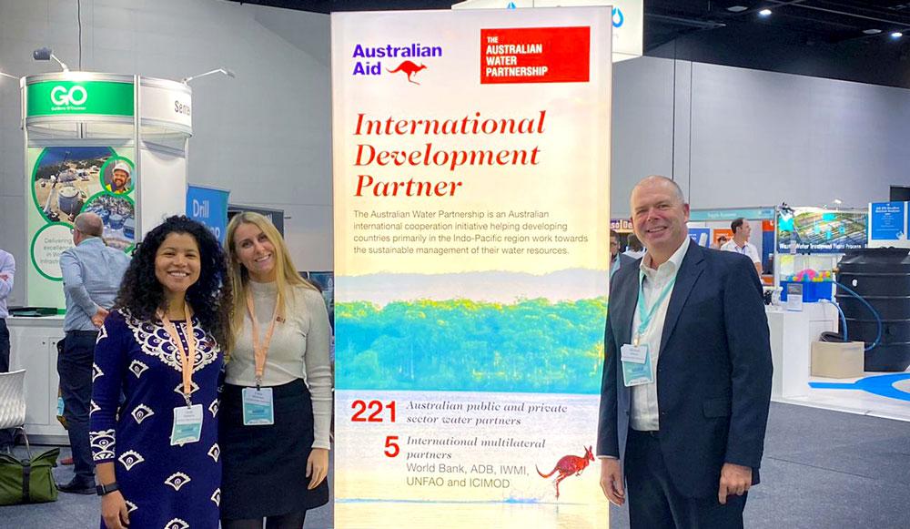 AWP team standing next to its International Development Partner banner